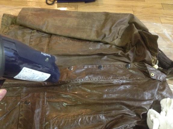 Barbour(バブアー/バーヴァー)のオイルドジャケットにオイルを塗り、ドライヤーでなじませているところ